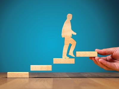Wooden cutout figure of a person climbing steps, with a hand holding up the last step