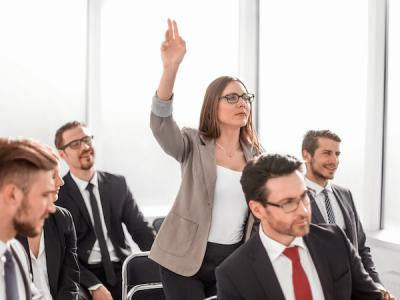 Business woman in a presentation audience standing and raising her hand to ask question