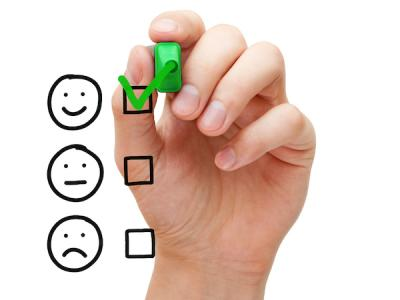 Hand checking the box next to a smiley face on a glass board, with two other options of a non-smiling face and a frowning face