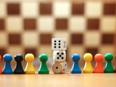 Game pieces and dice arranged in front of a chess board