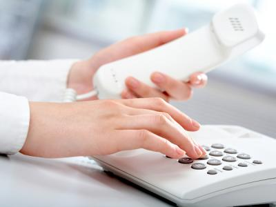 Woman's hands in a business setting holding a phone receiver in left hand and pushing numbers on the phone with right hand