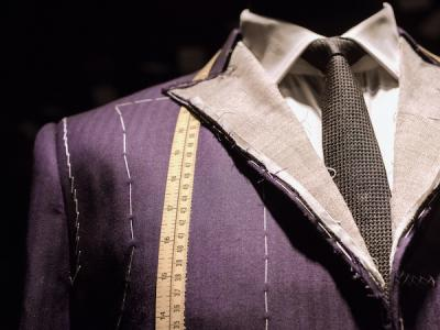 Partly finished man's suit on a tailor's dummy with chalk markings and a measuring tape