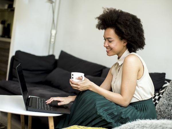 Woman sitting on a sofa looking at a laptop and holding a cup of coffee