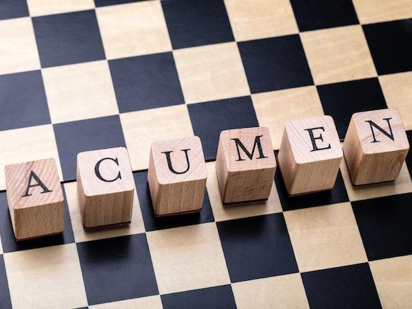 The word ACUMEN spelled with wooden blocks on a chess board