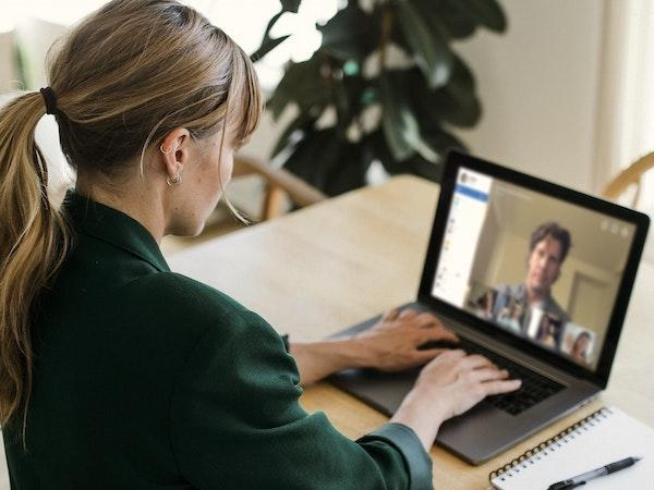 Woman with a laptop participating in a virtual meeting