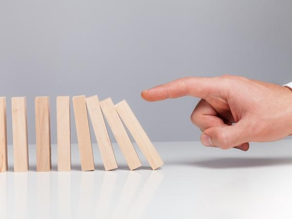 Finger causing the first domino in a row to start falling
